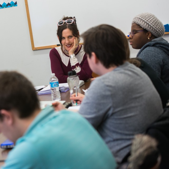A smiling female-presenting professor sits at the head of a cozy table surrounded by students engaged in discussion.