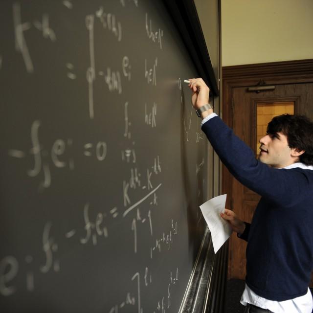 A male teacher writes equations on a blackboard in a classroom.