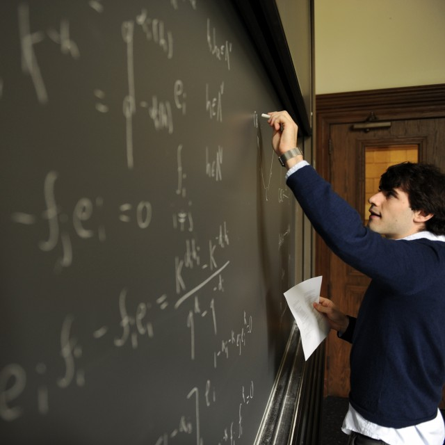 A male teacher writes equations on a blackboard in a classroom.
