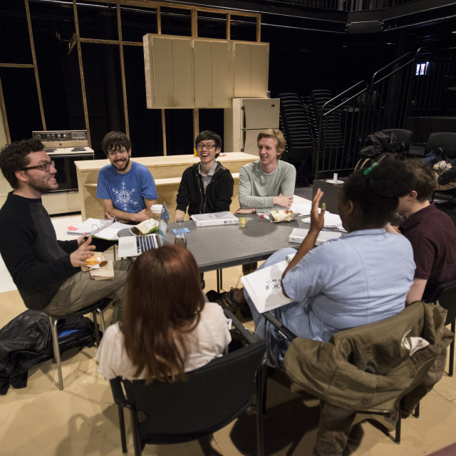 Theater students sit around a table in a sparse kitchen set, with an empty audience.