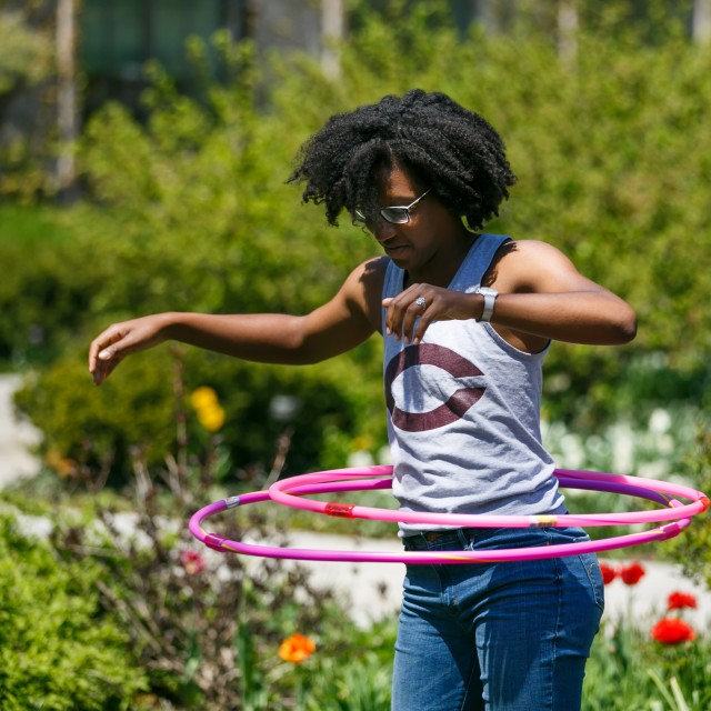 A female student hula hoops amongst flowers on a sunny day.
