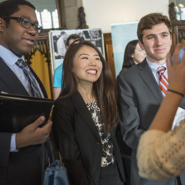 Three students speak with a recruiter around a table during a career fair.