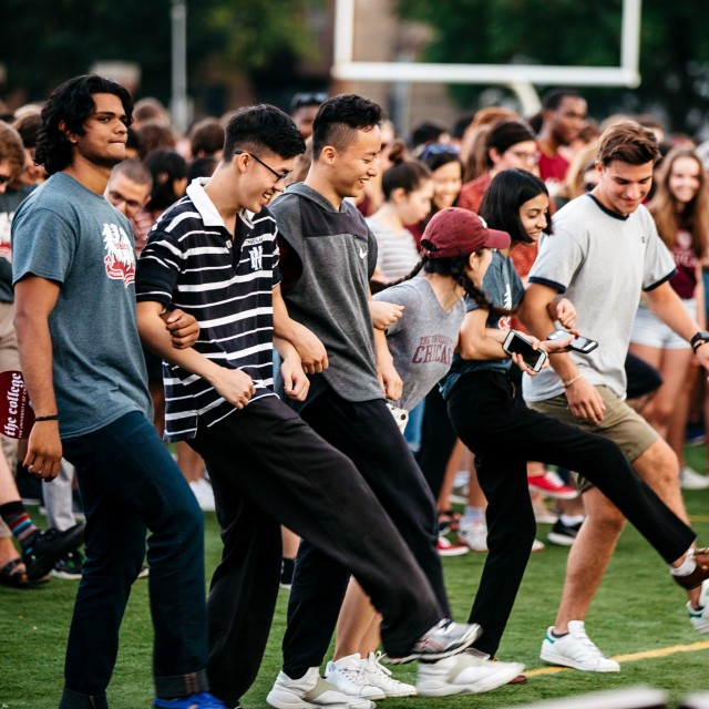 A group of students dance on a football field in front of a large crowd of other students.