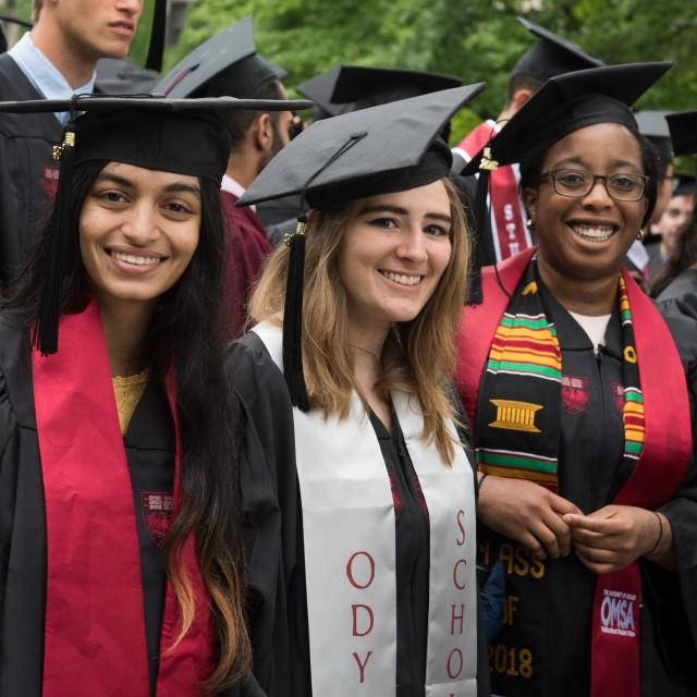 A group of students in graduation cap and gown on a sunny day. The focus is on three female-presenting people smiling at the camera.