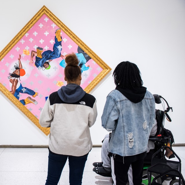 A group of five students view a brightly colored piece of art that is hanging sideways on a wall in a museum.