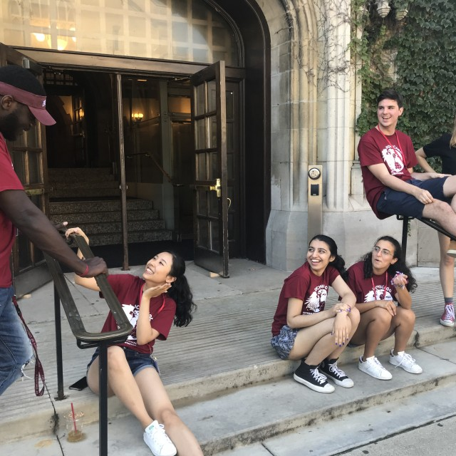 A group of grinning students in Orientation Team t-shirts sit on the front stairs and railings of Reynolds Club.