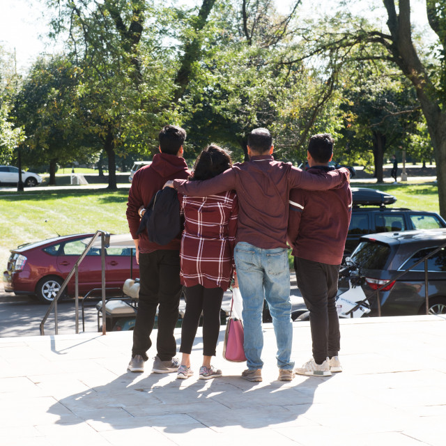 A family wearing maroon is shown embracing.