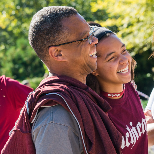 Man with arm around younger woman wearing Uchicago shirt.