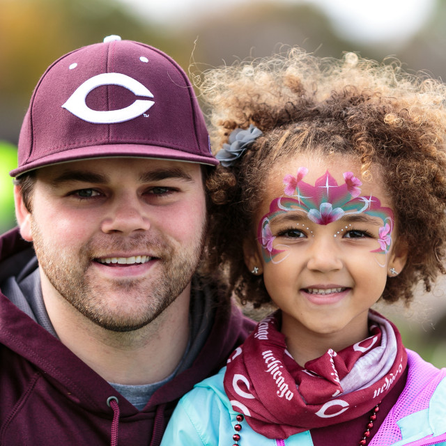 "A young man in a maroon hat with the UChicago ""C"" logo on it posts with a little girl with floral facepaint on her face and a UChicago bandana around her neck."