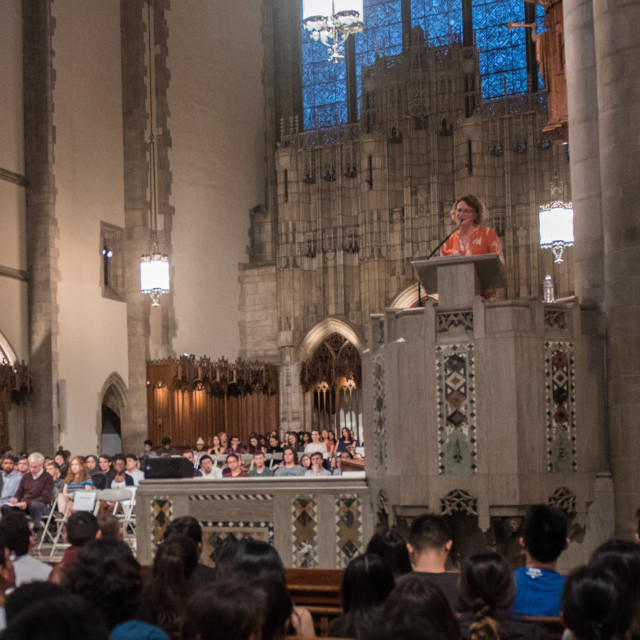 A speaker stands at the pulpit of Rockefeller chapel with a full audience.
