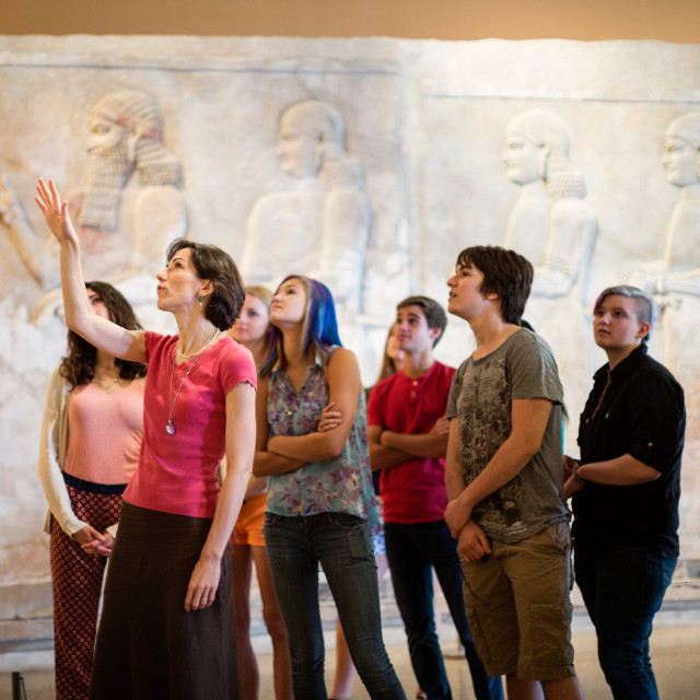 An instructor in a museum speaks to a group of students, pointing upward to something out of frame.