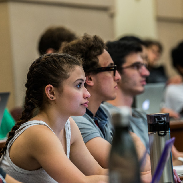 Attentive students sit in a row at a table, with laptops and water bottles.