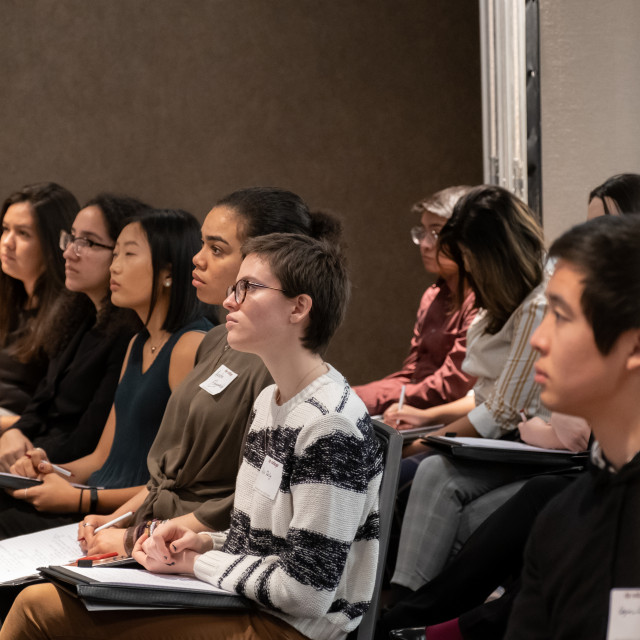 Students sitting at individual tablet arm chairs look attentive.