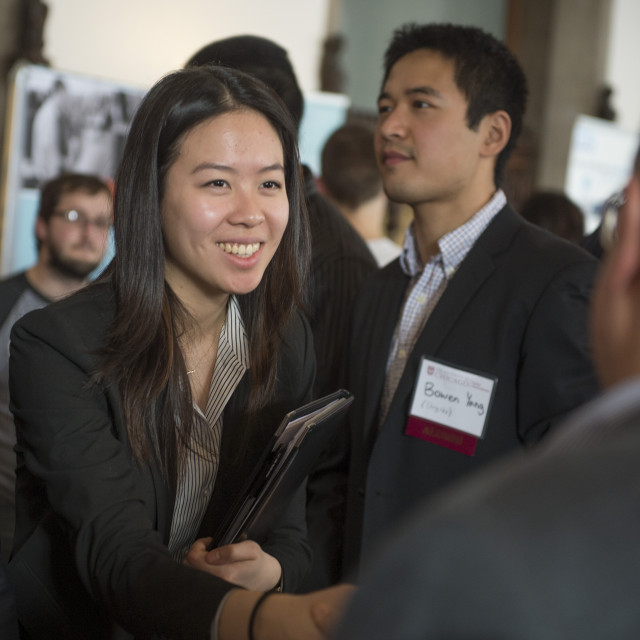 A student shakes hands with someone at a career fair.