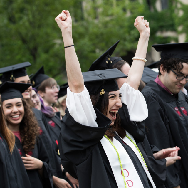 A student wearing a cap and gown celebrates during a convocation ceremony.