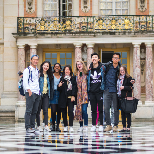 Students stand in front of a classical style building with balconies.
