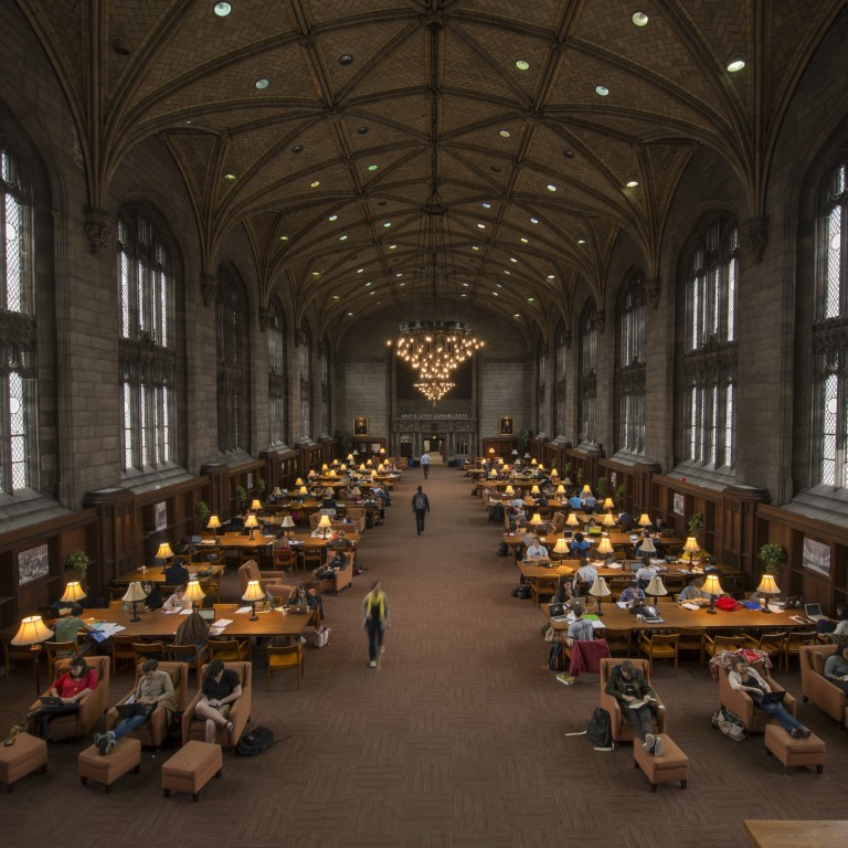 Students study at tables in the picturesque Harper Library.