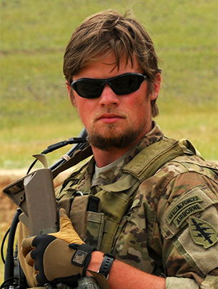 A man wearing Army fatigues and sunglasses is pictured outside.