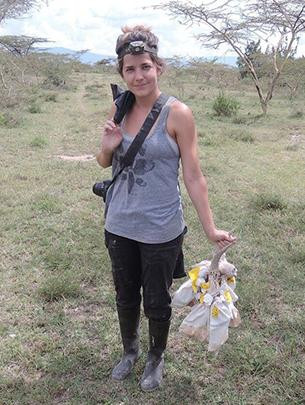 Holly Lutz stands in a grassy field with gear in hand.