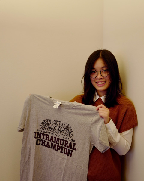 """A student stands holding a tshirt that reads """"Intramural Champion"""""""
