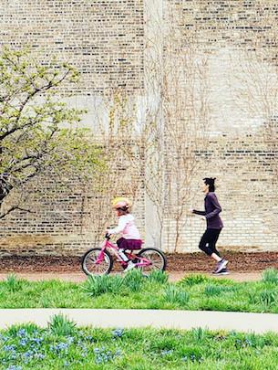 Sabina Shaikh runs behind her daughter as she rides a bikes near a large stone wall.