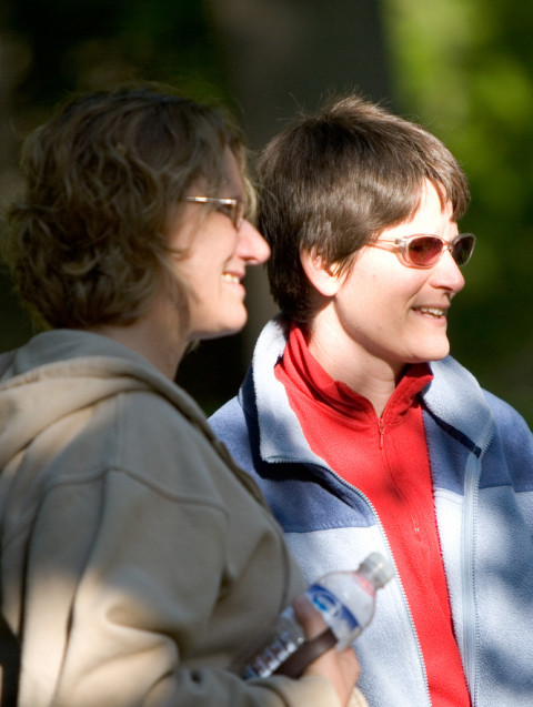 Two people are shown outside on a sunny day. The person on the right (Kathy Forde) is wearing red-tinted sunglasses.