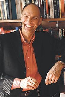 Portrait of Andreas Glaeser in front of shelves of books.