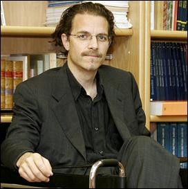 A male-presenting person sits in front of a bookshelf.