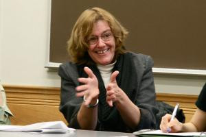Candace Vogler spreads her hands sitting at a table in a classroom.
