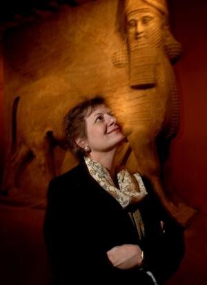 Martha Roth stands near sculptures in the Oriental Institute.