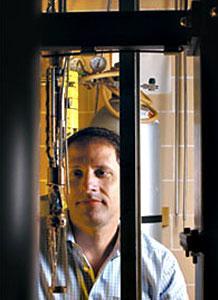 Thomas Rosenbaum stands near equipment in lab like environment.