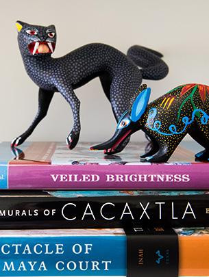 Two brightly colored figurines of fantastical animals are shown atop a stack of books.