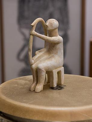 A small stone sculpture of an harpist sits atop a drum.