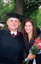 A man and woman pose wearing black graduation robes. The woman holds flowers.