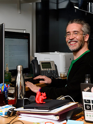 A profesor sits at a desk in front of two computer screens and a phone.