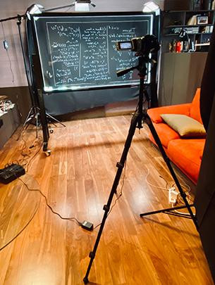 A camera is shown in a makeshift studio pointing at a clear marker board used to film lectures for a class.