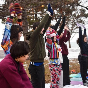 A group of students wearing colorful outdoor gear stretch while doing yoga outdoors on a winter day.