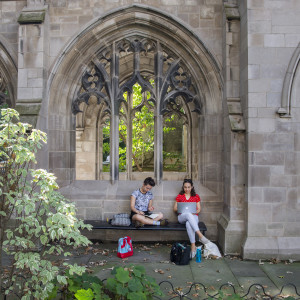 Two students study outside under a gothic arch of a building.