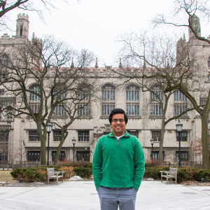 A student wearing a green sweater stands in front of a gothic building on UChicago's campus.