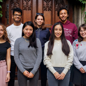 The College Editorial team, comprised of several students, pose together in front of wooden doors and ivy-covered walls.