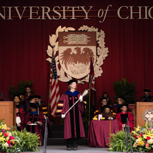 "A group of faculty are shown standing on a graduation stage with a maroon curtain and a large crest with ""The University of Chicago"" displayed above them."