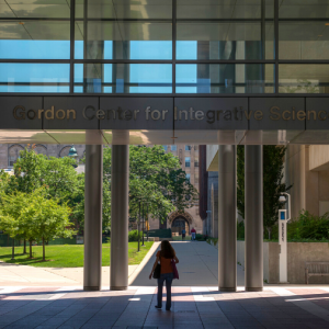 Glass archway of the Gordon Center. A person walks through the center, and green grass and trees are visible in the distance.