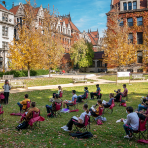 Sunny image on the quad of an outdoor class with rows of students listening to the professor.