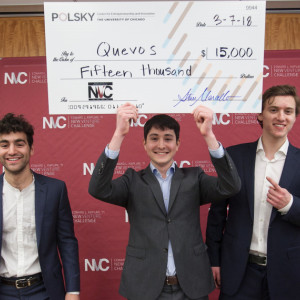 Three students wearing suits stand in front of a large banner holding a giant check for $15,000.
