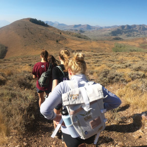First-year women hike on the open trails in Utah, carrying backpacks and dressed in workout gear.
