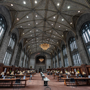 A large gothic room is shown students studying at tables with lamps.