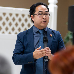 Rep. Andy Kim speaks in front of an audience during a town hall with a white picket room divider in the background.