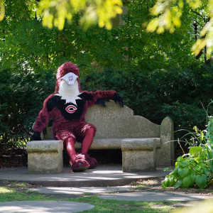 A person wearing a giant Phoenix mascot costume with a UChicago tshirt and face mask sits on a stone bench in a garden.
