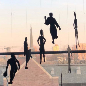 Black cut-out paper figures hang from the window