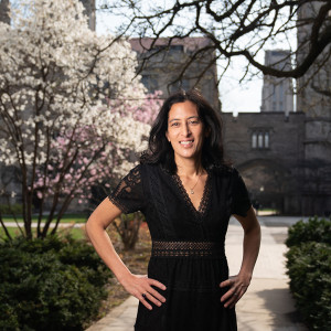 A portrait of Sabina Shaikh standing on a campus quadrangle with blooming cherry blossom trees in the background.